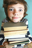 preteen handsome boy with book pile
