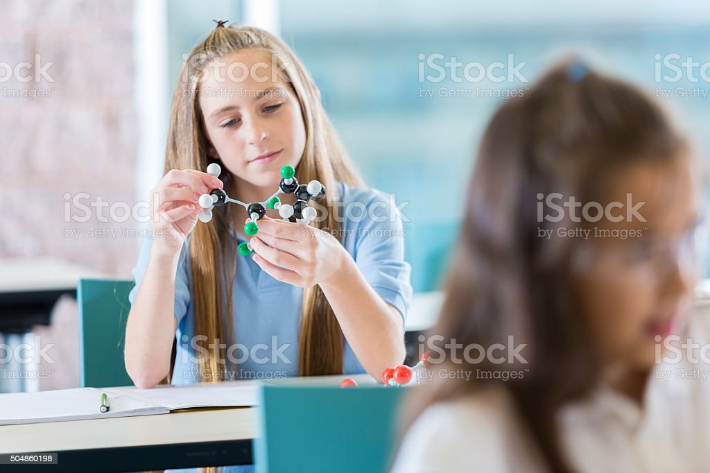 Preteen student studying molecules in science lab classroom stock photo