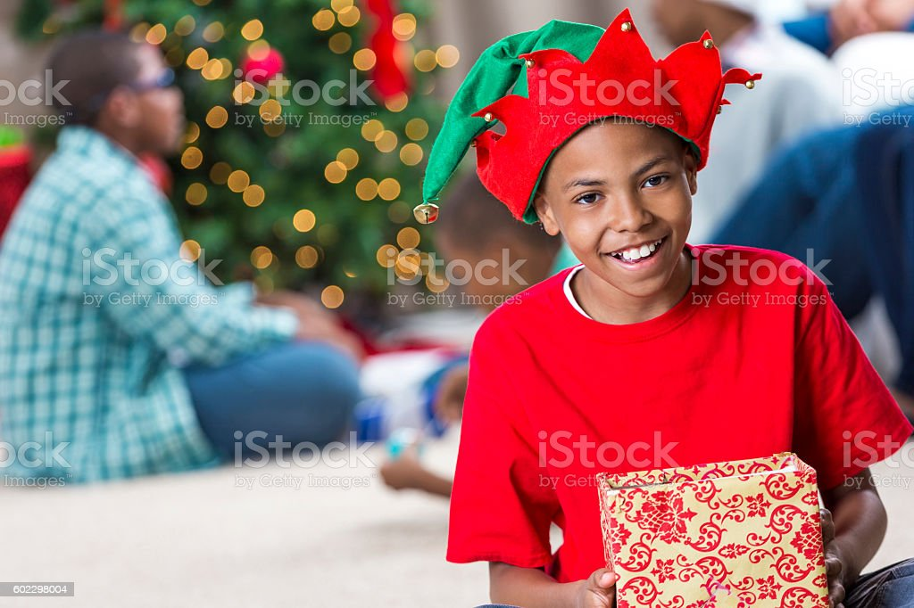 Preteen wearing an elf hat and holding a Christmas present stock photo