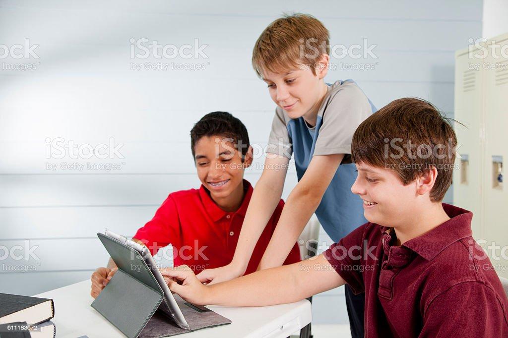 Pre-teenage friends using digital tablet, internet, social media. stock photo
