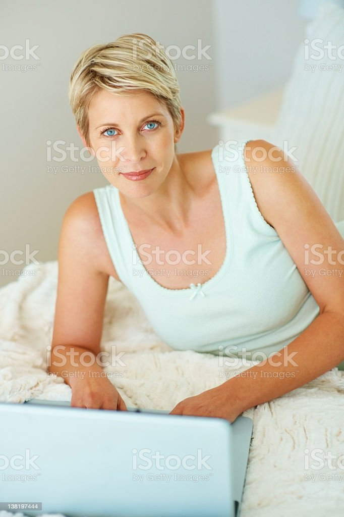 Prette mature woman using laptop in bed looking to camera royalty-free stock photo