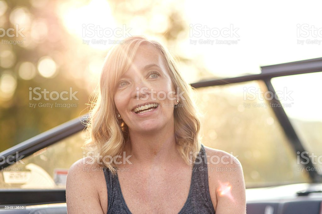 Pretty adult female smiling in a boat stock photo