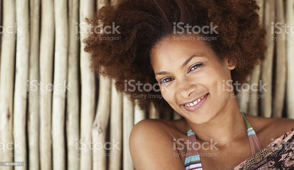 Pretty African American female against a bamboo wall royalty-free stock photo
