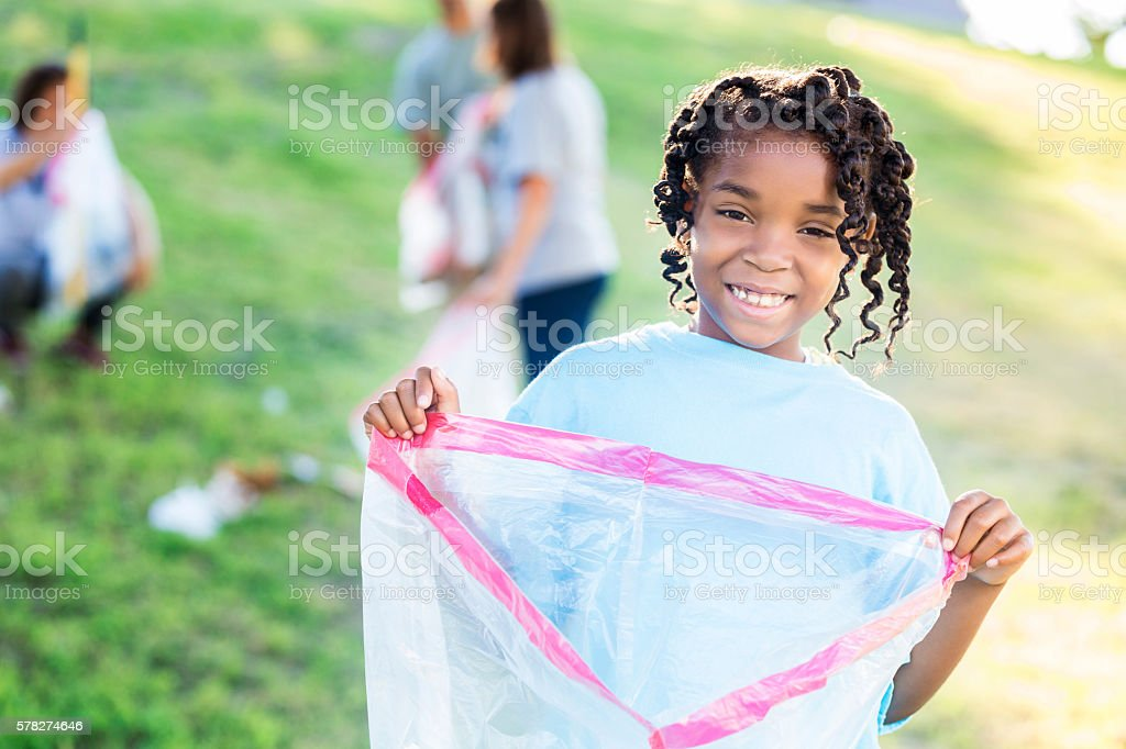 Pretty African American Girl volunteering at park clean-up stock photo