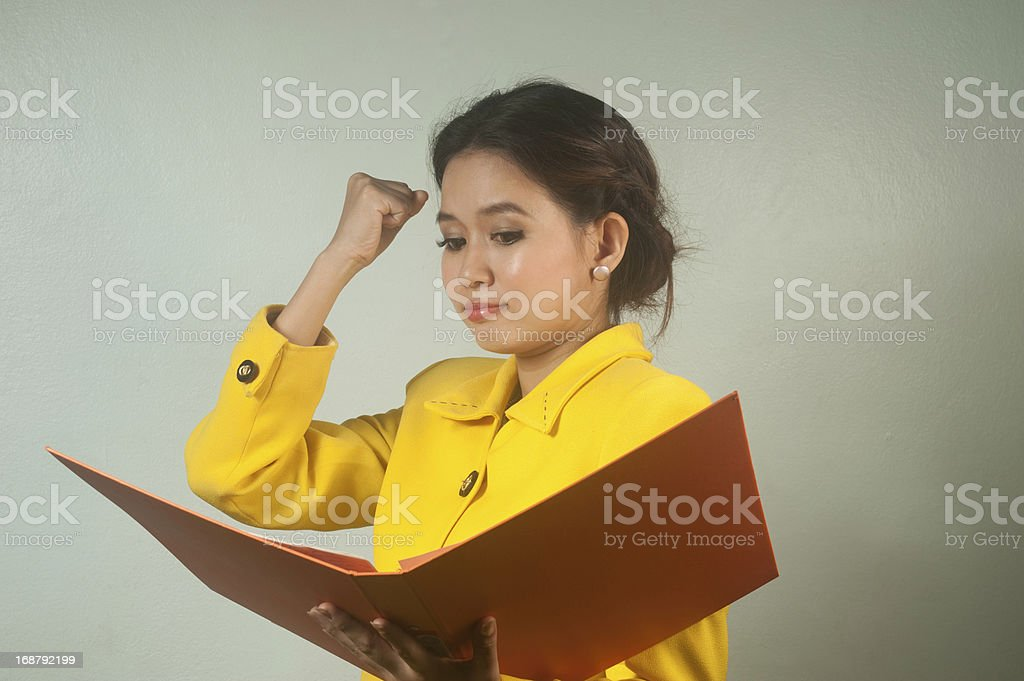 Pretty Asian businesswoman complacent reading a file. royalty-free stock photo