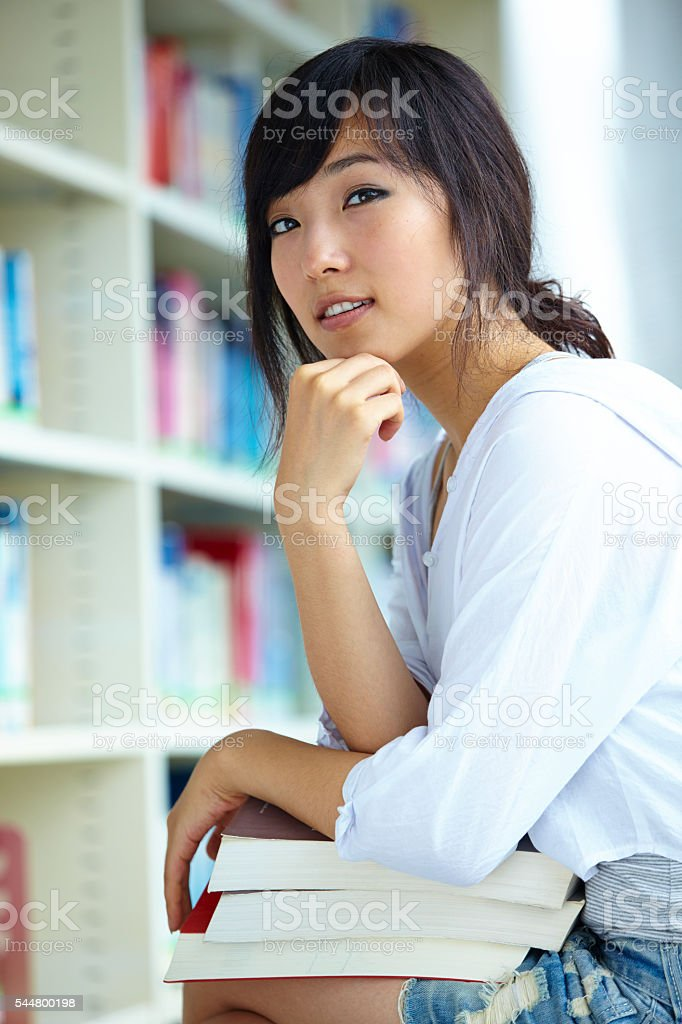 pretty Asian college student in library stock photo