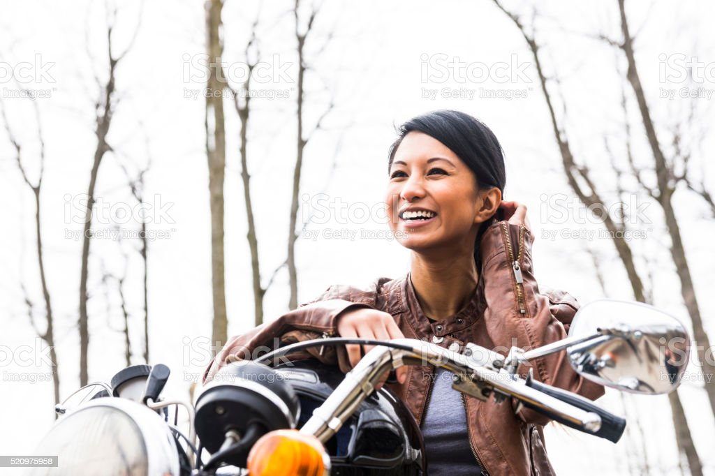 Pretty Asian woman astride a motorcycle stock photo