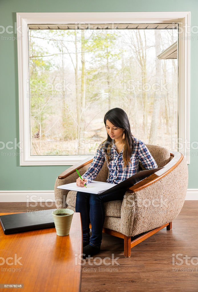 Pretty Asian woman sketching at home. stock photo
