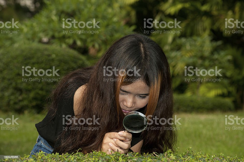 Pretty Asian woman with magnifying glass . royalty-free stock photo