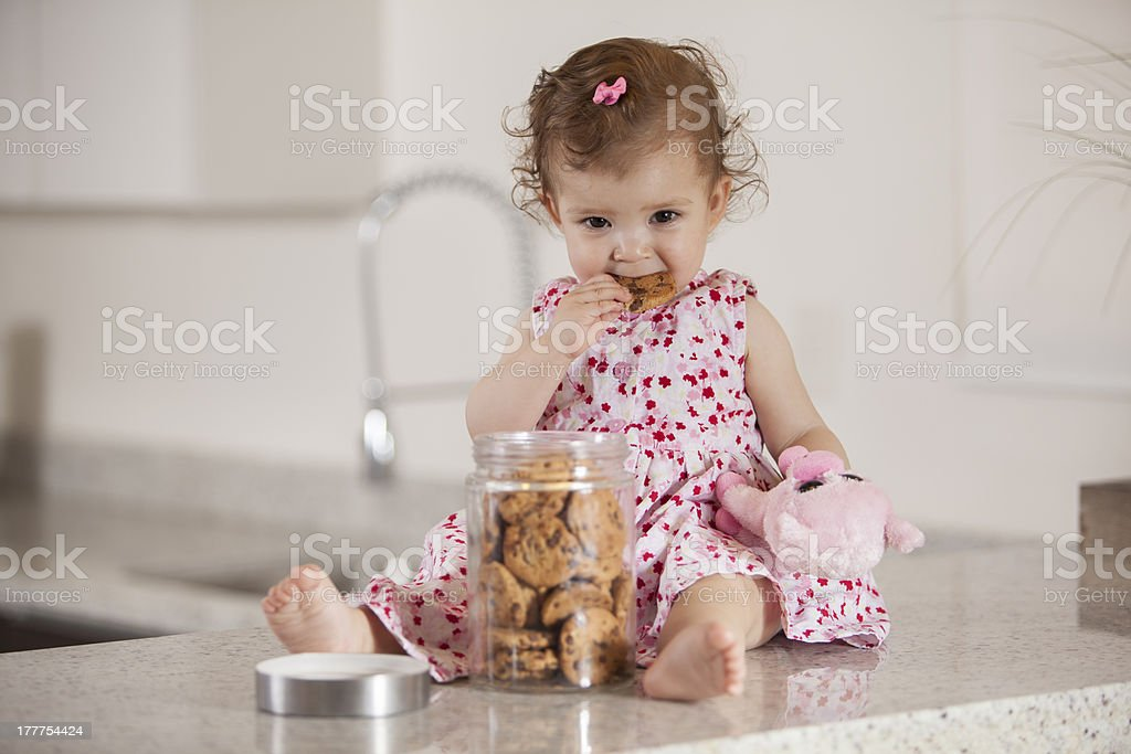 Pretty baby girl eating cookies from a jar royalty-free stock photo