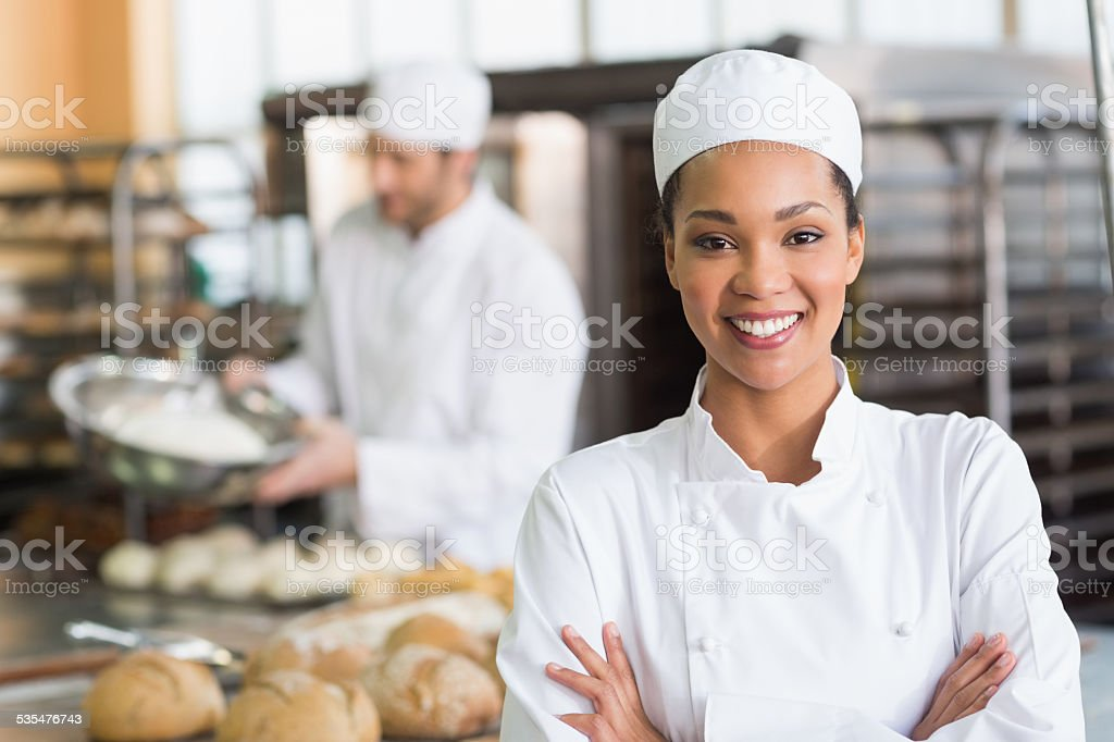 Pretty baker smiling at camera stock photo