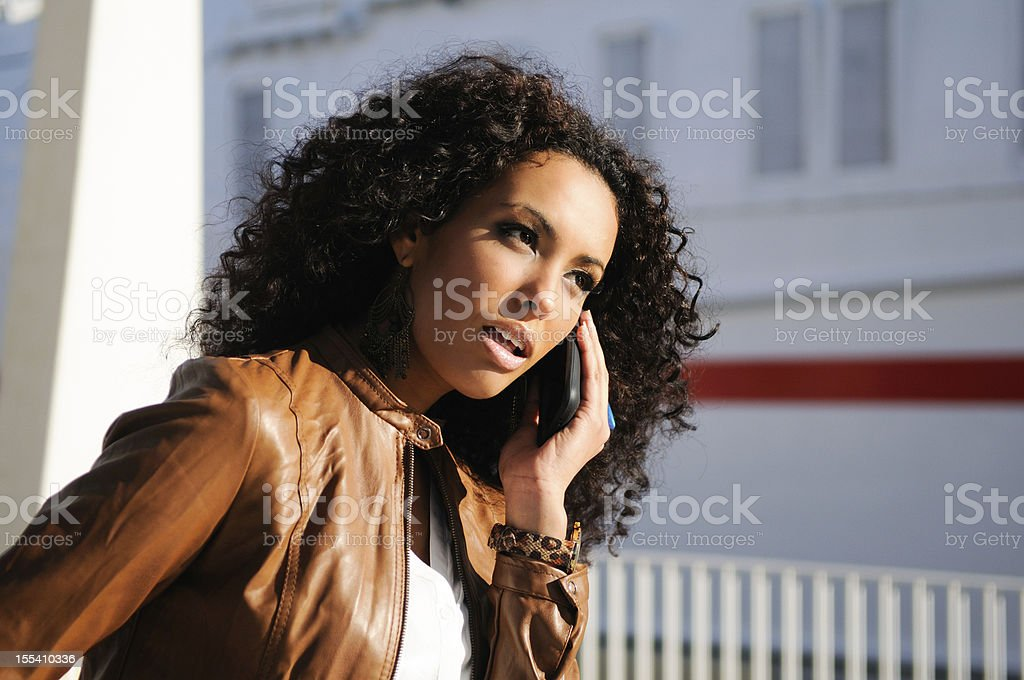 Pretty black woman in urban background talking on phone royalty-free stock photo