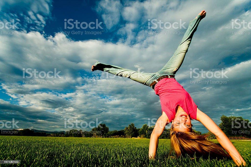 Pretty Blond Caucasian Girl Doing a Cartwheel stock photo