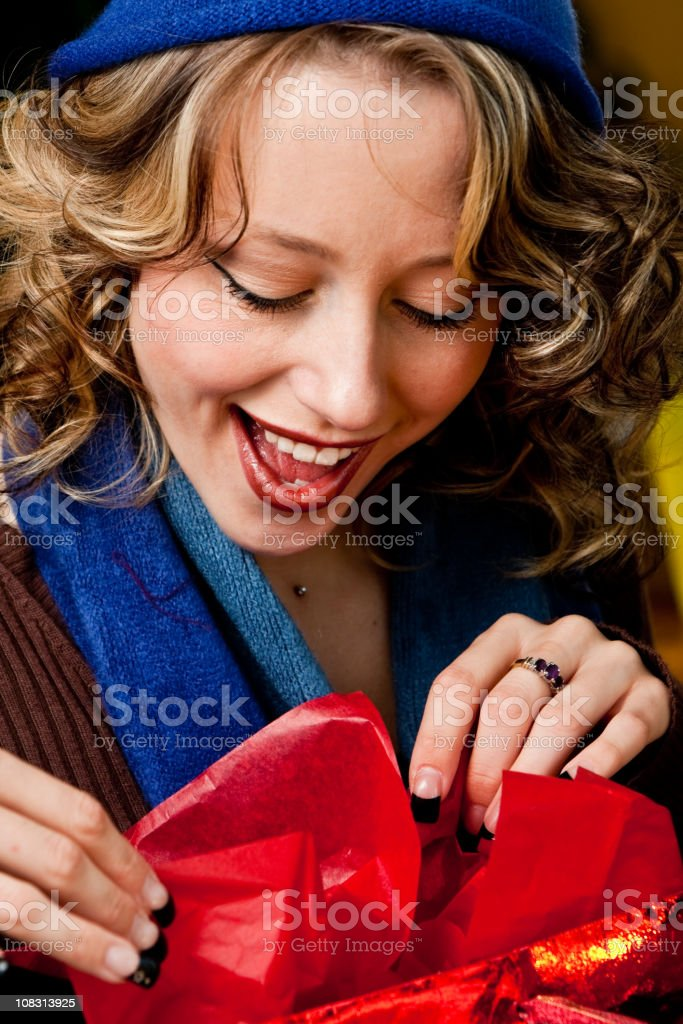 Pretty Blond Girl in Knit Hat Opening Gift royalty-free stock photo