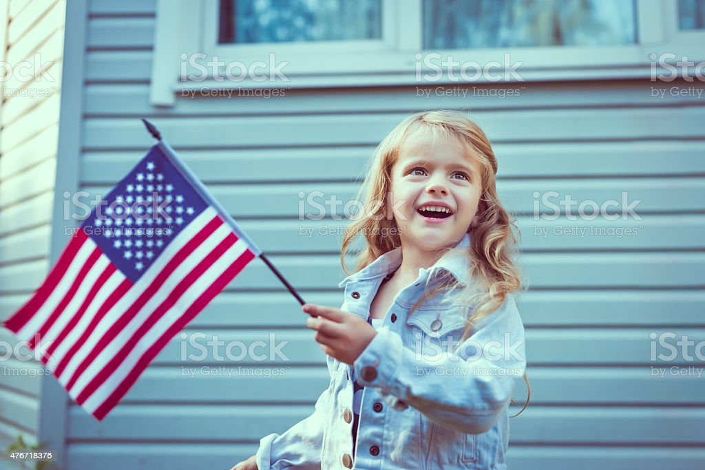 Pretty blond little girl smiling and waving american flag stock photo