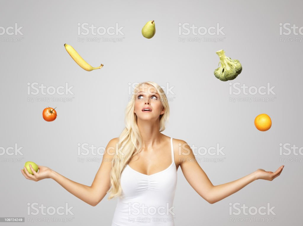 Pretty blond woman juggling fruits royalty-free stock photo