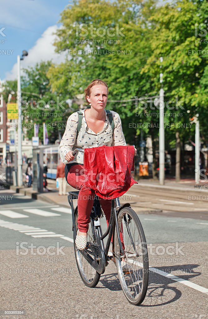 Pretty blond young woman on her bicycle with red jacket stock photo