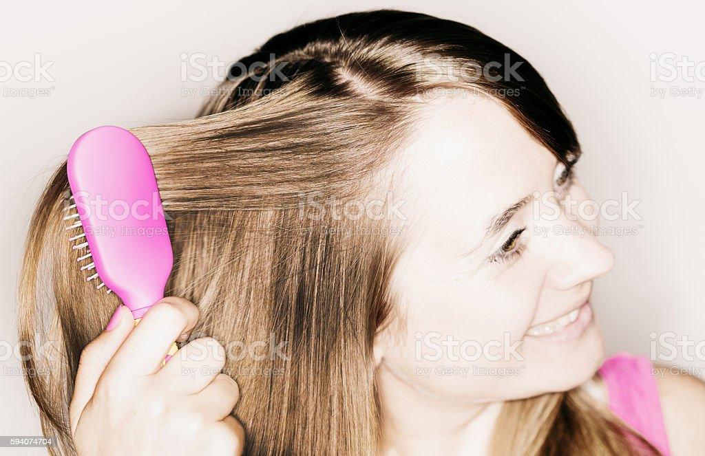 Pretty blonde brushing her long, thick, beautiful hair stock photo