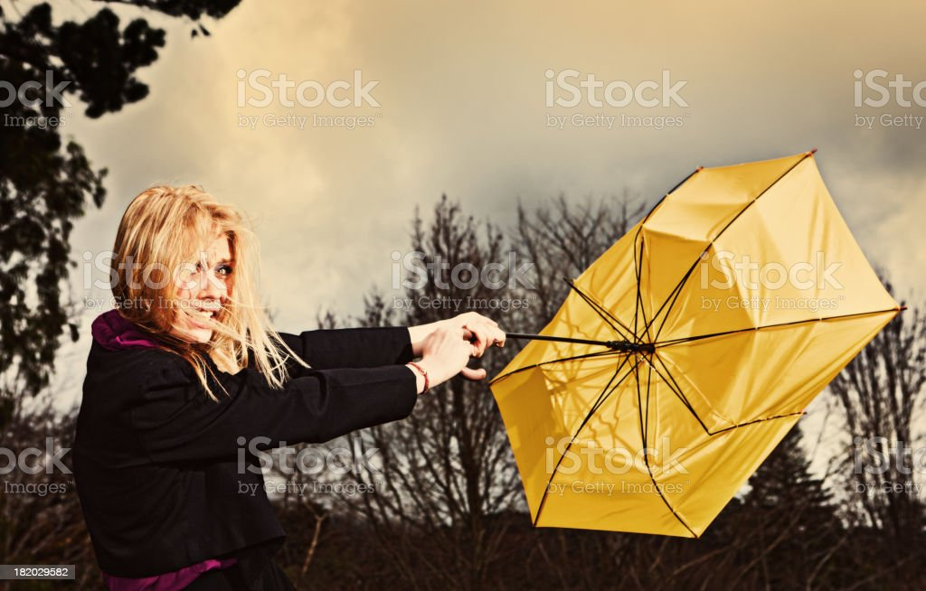 Pretty blonde desperately wrestling with umbrella in storm stock photo