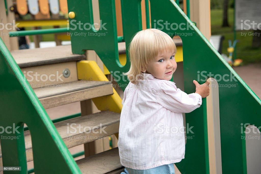 Pretty blonde girl go up stairs in children playground stock photo
