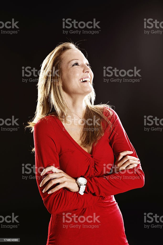 Pretty blonde in red laughs against black background stock photo