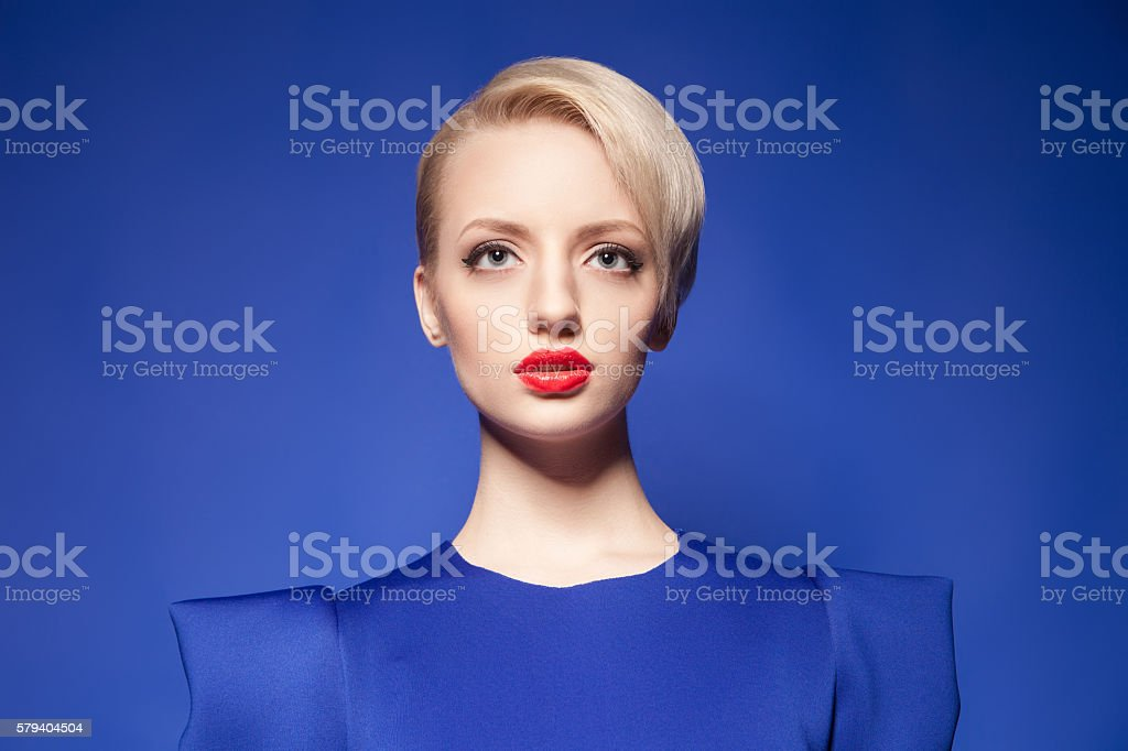 Pretty blonde model with fashion hairstyle against of blue backgound stock photo