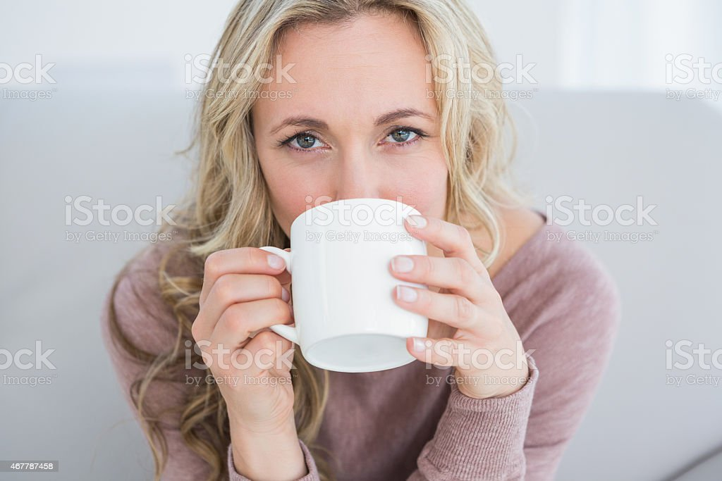 Pretty blonde on couch drinking hot drink stock photo
