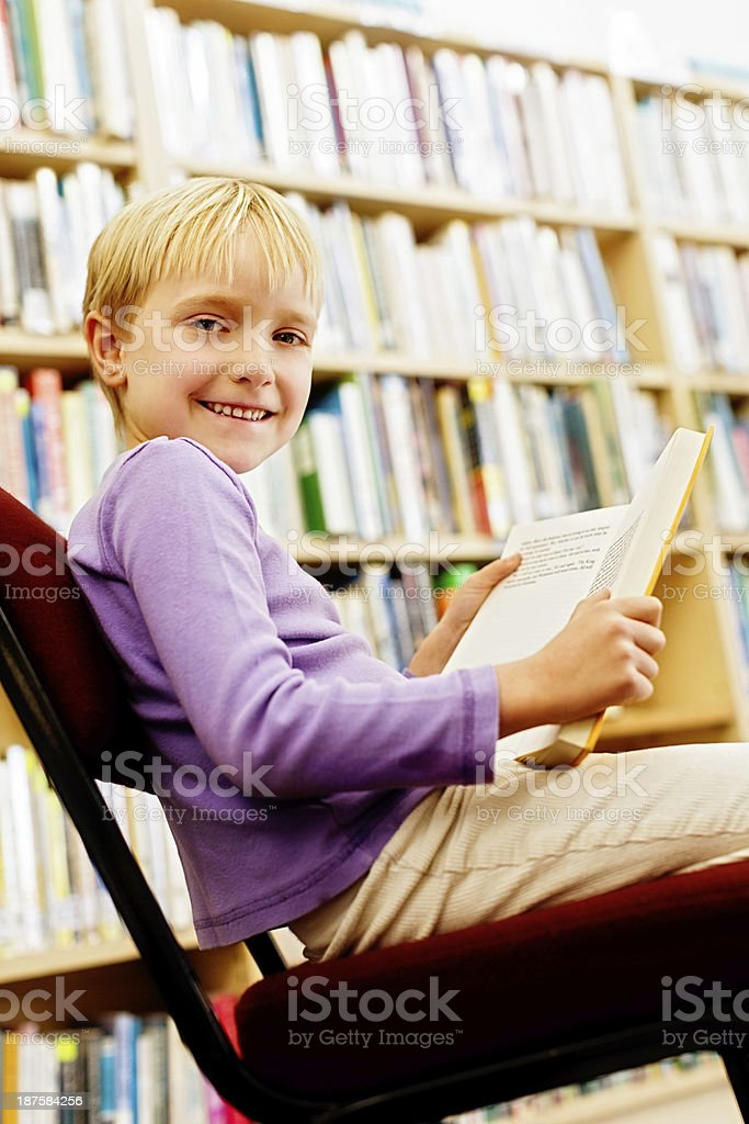 Pretty blonde schoolgirl happily reading in library royalty-free stock photo