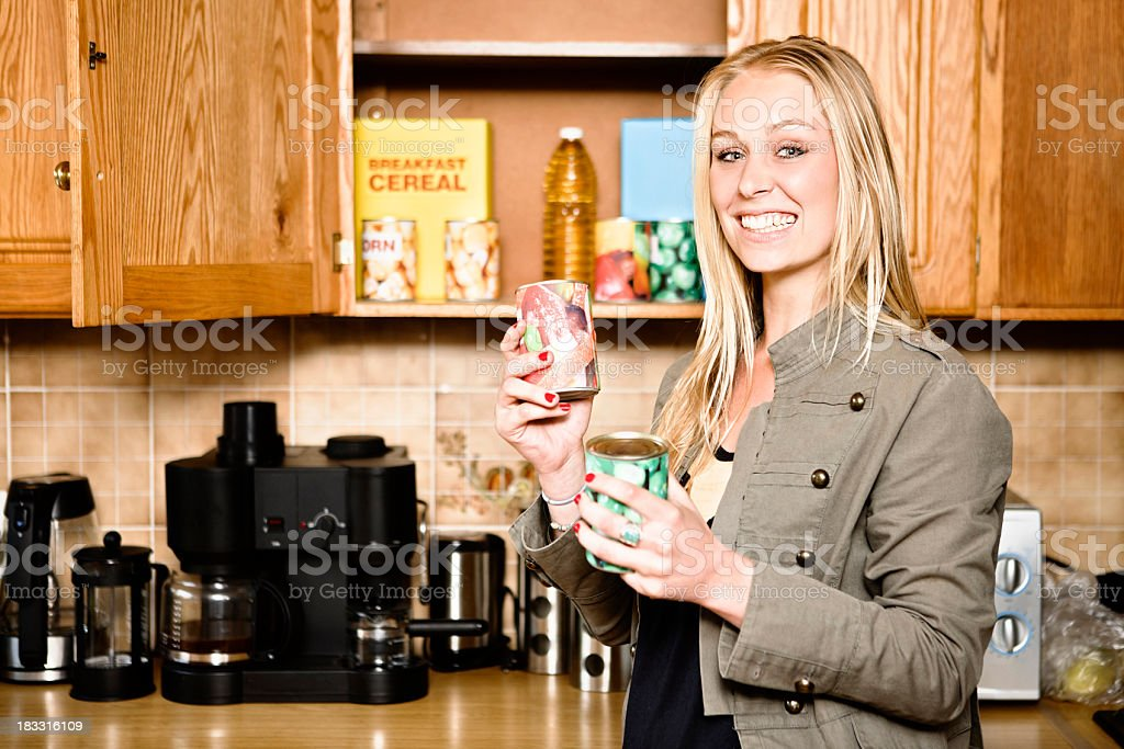 Pretty blonde smiles, holding canned food from kitchen cupboard stock photo