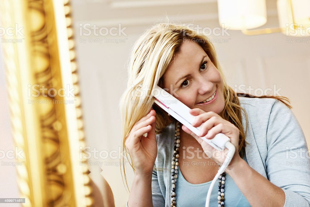 Pretty blonde styling her hair before gilt-framed mirror royalty-free stock photo