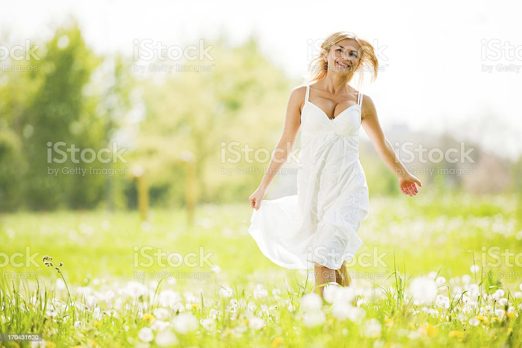 Pretty blonde wearing white dress is walking in the park royalty-free stock photo