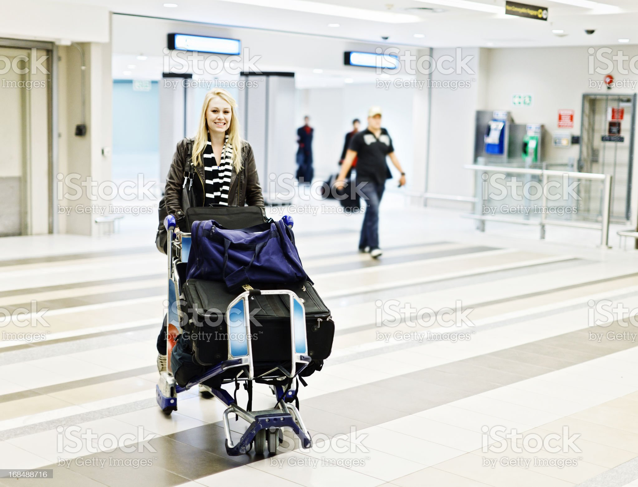 Pretty blonde wheels her laden luggage cart through airport concourse royalty-free stock photo