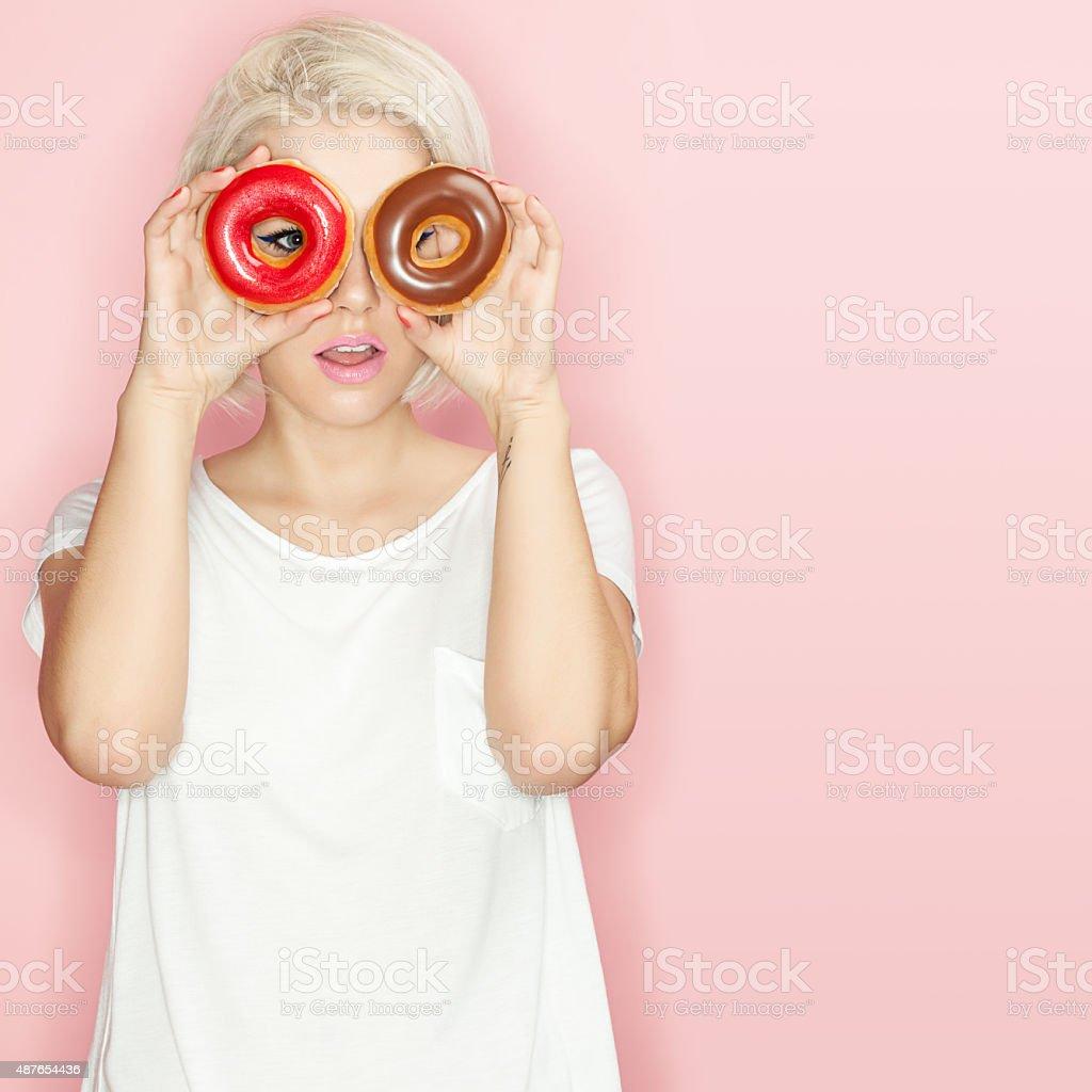Pretty blonde  with multi-colored donuts stock photo