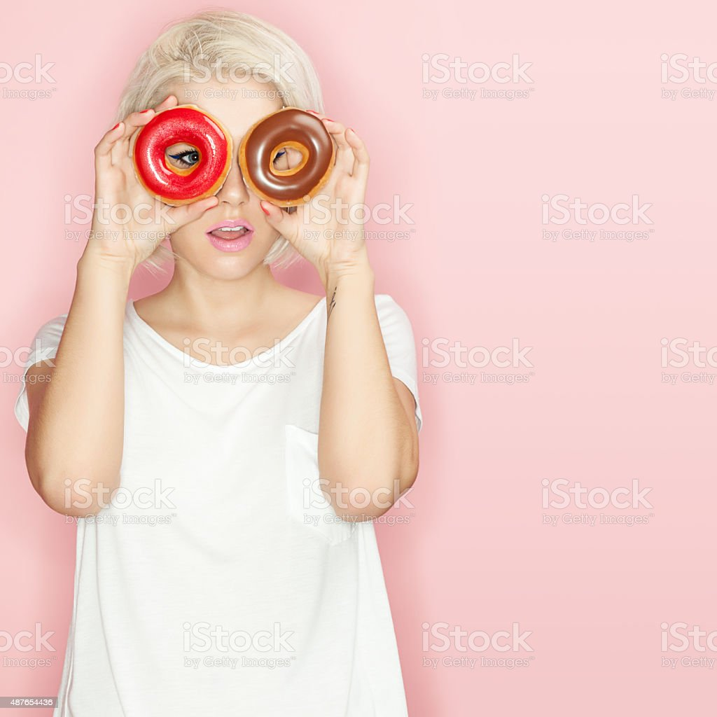 Pretty blonde  with multi-colored donuts stock photo