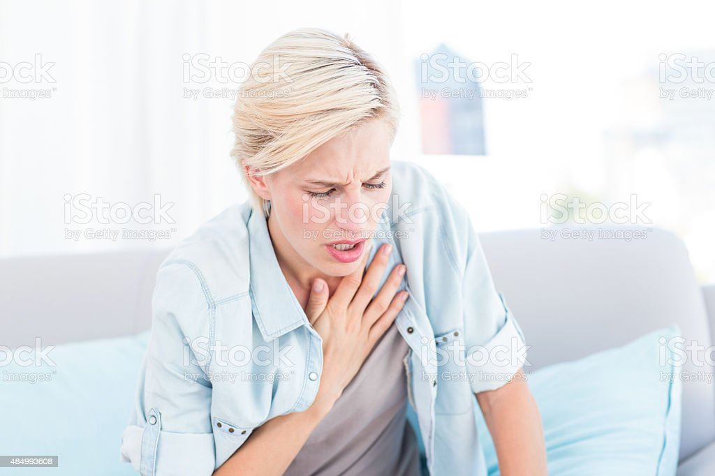 Pretty blonde woman having breath difficulties stock photo