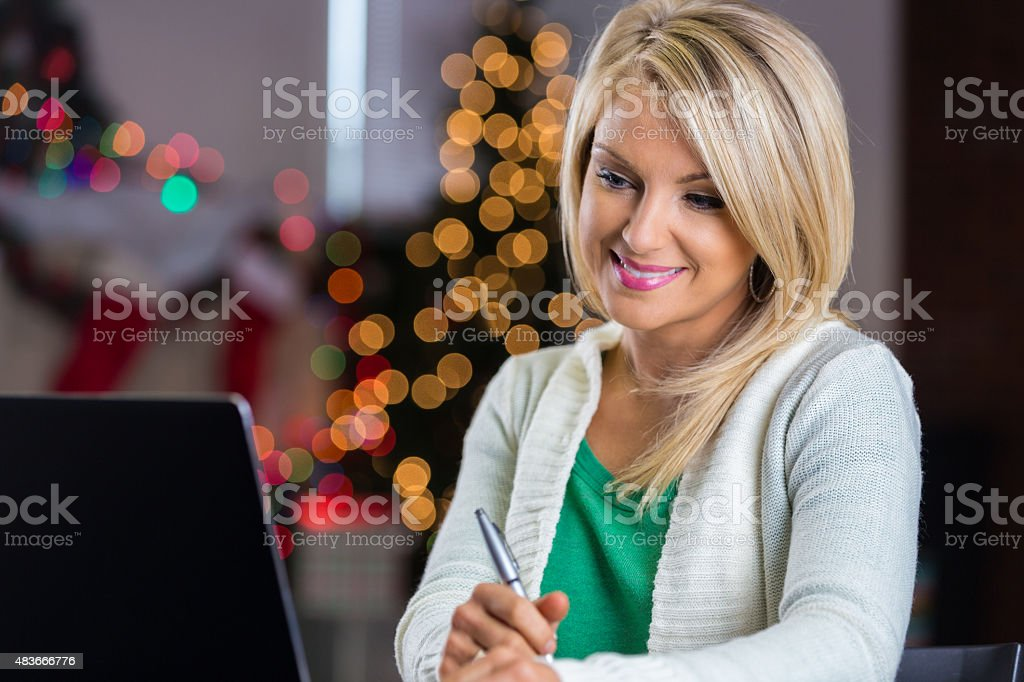Pretty blonde woman making Christmas list while shopping online stock photo