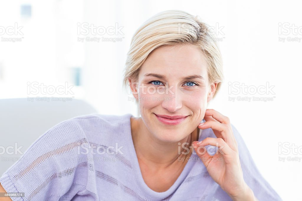 Pretty blonde woman smiling at camera on sofa stock photo