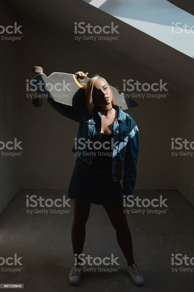 Pretty blonde woman with longboard in dark room stock photo