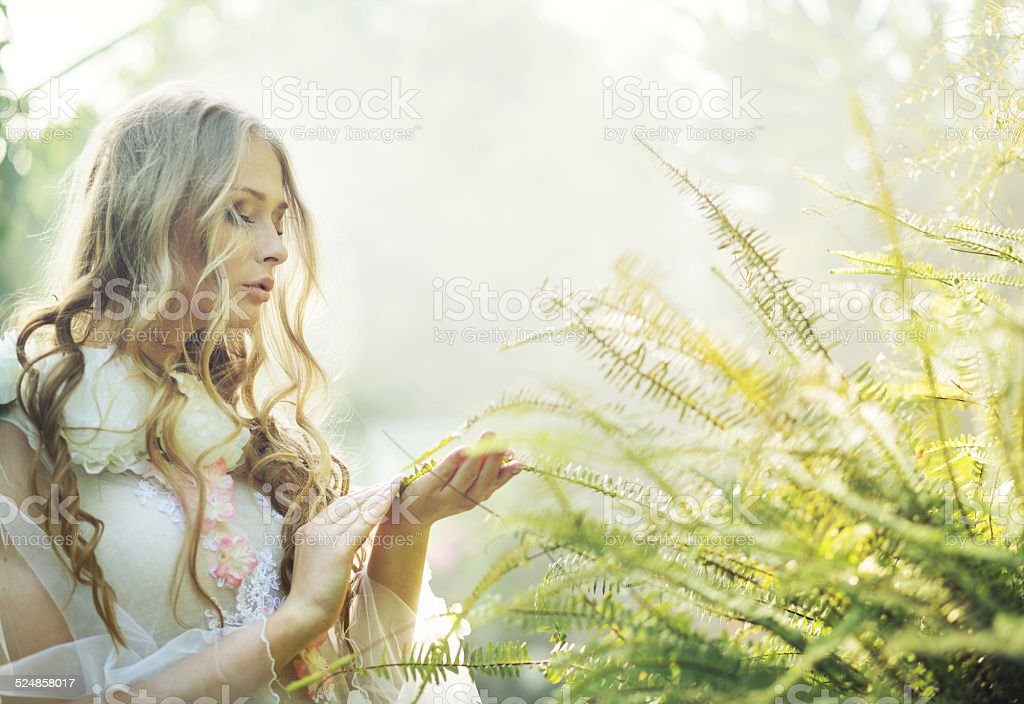 Pretty blonde woman with the fern stock photo