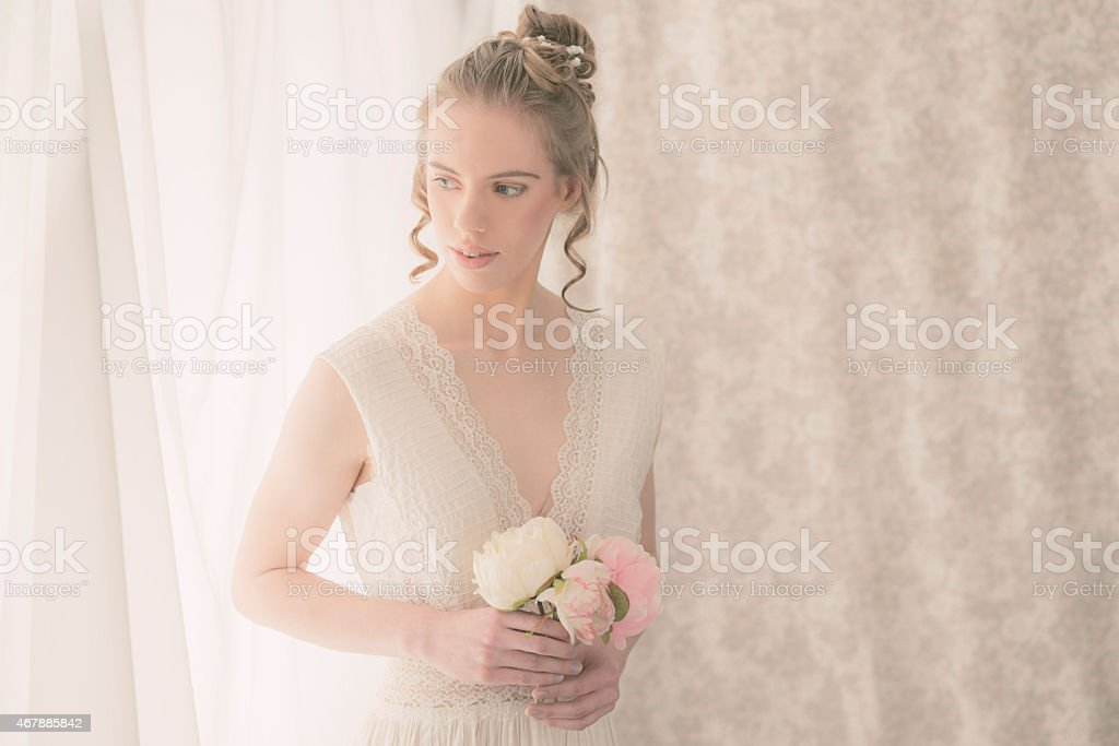 Pretty Bride Holding Bouquet of Roses in her Room stock photo