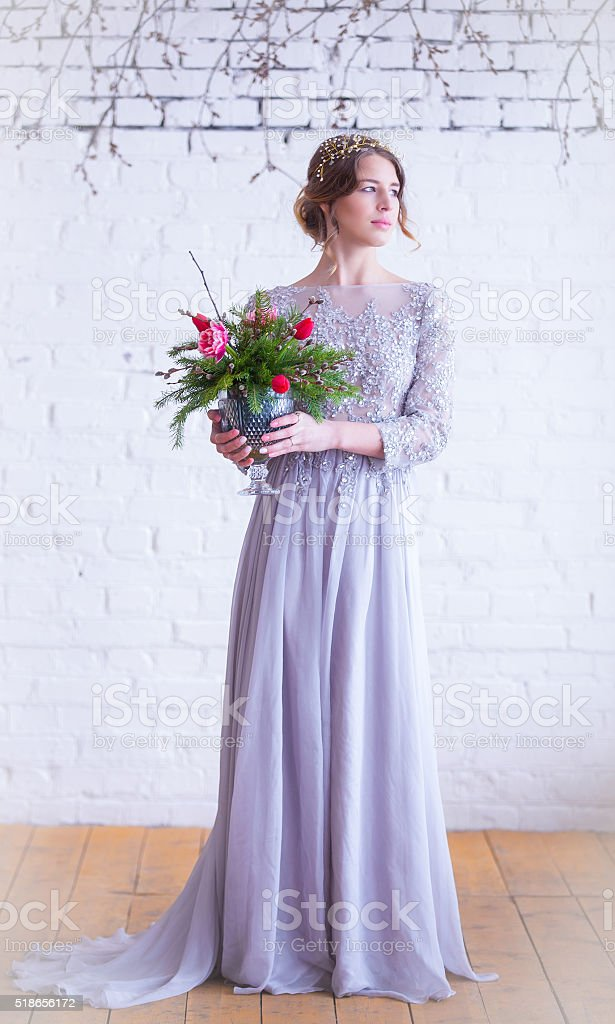 pretty bride in grey long dress with bouquet in vase stock photo