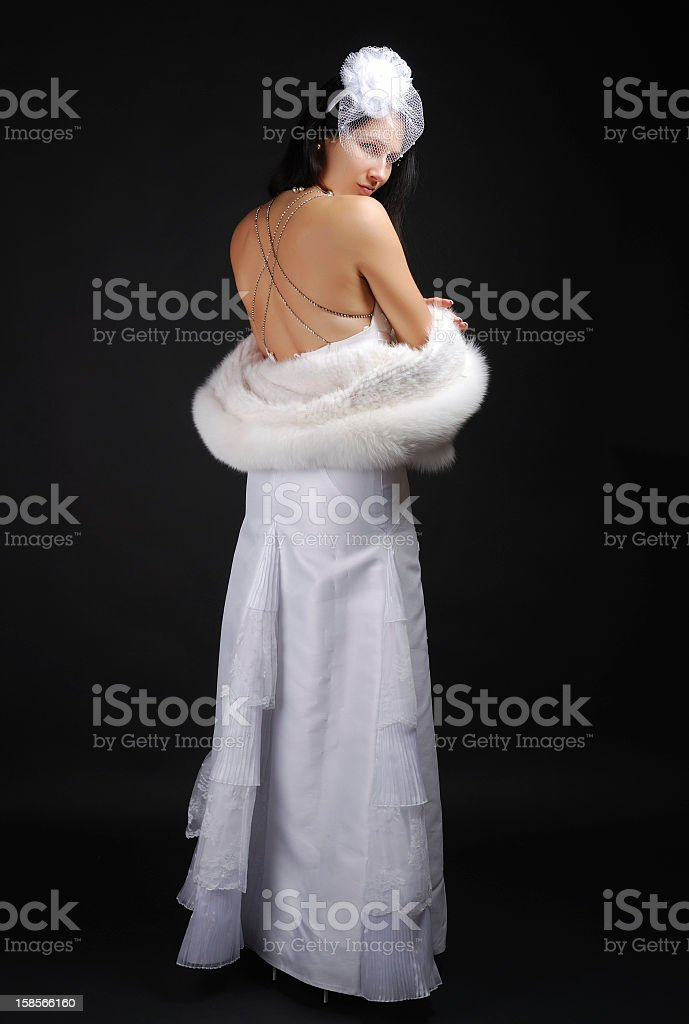 Pretty bride undressing fur coat. royalty-free stock photo
