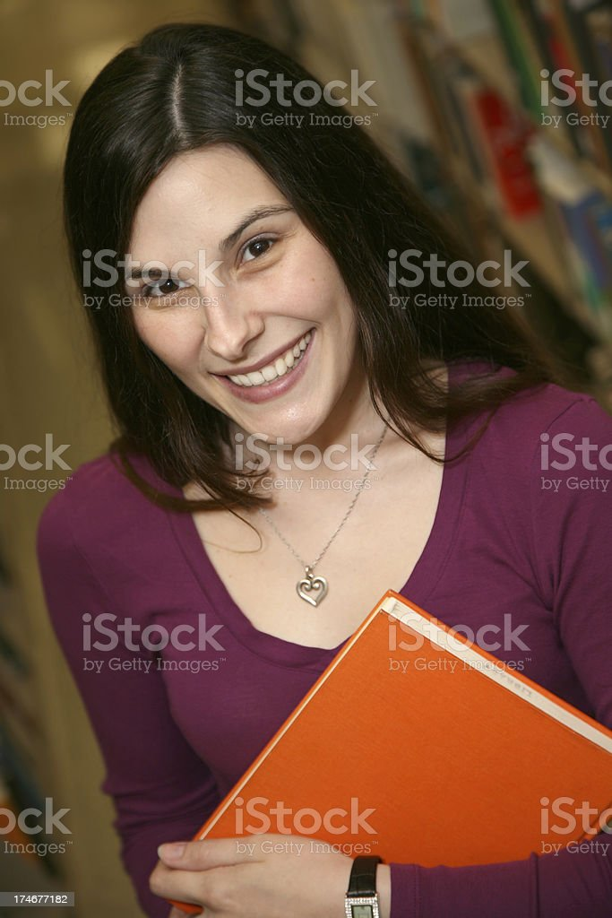 Pretty Brown Haired Female Student Holding Book in the Library royalty-free stock photo