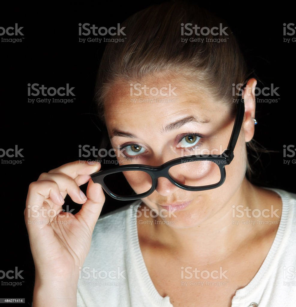 Pretty brown-eyed blonde looks over glasses smiling knowingly stock photo