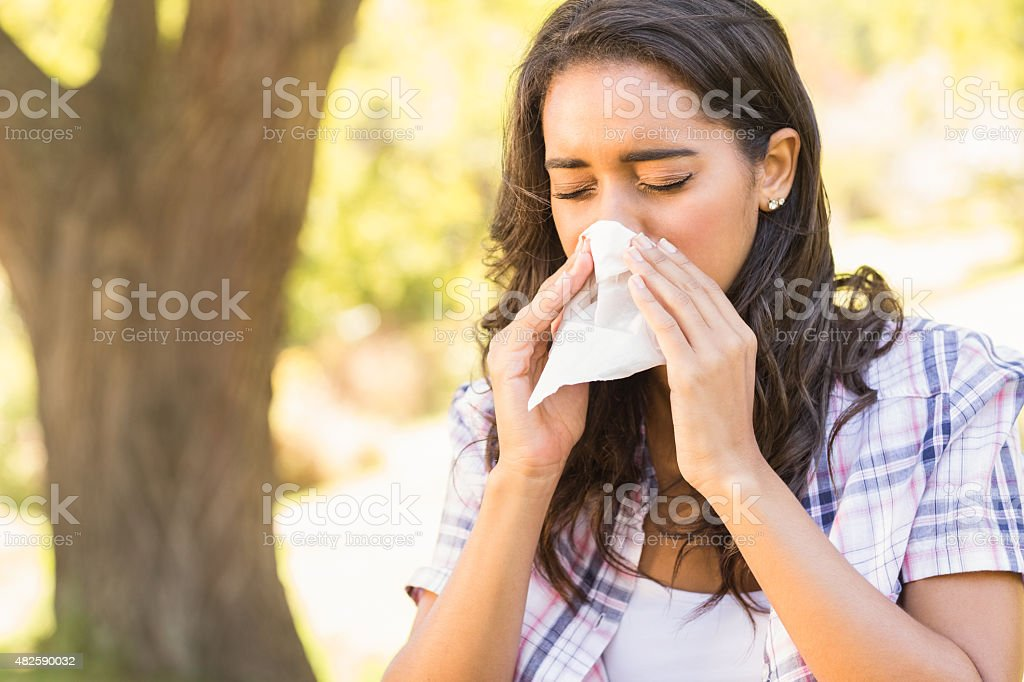 Pretty brunette blowing her nose stock photo