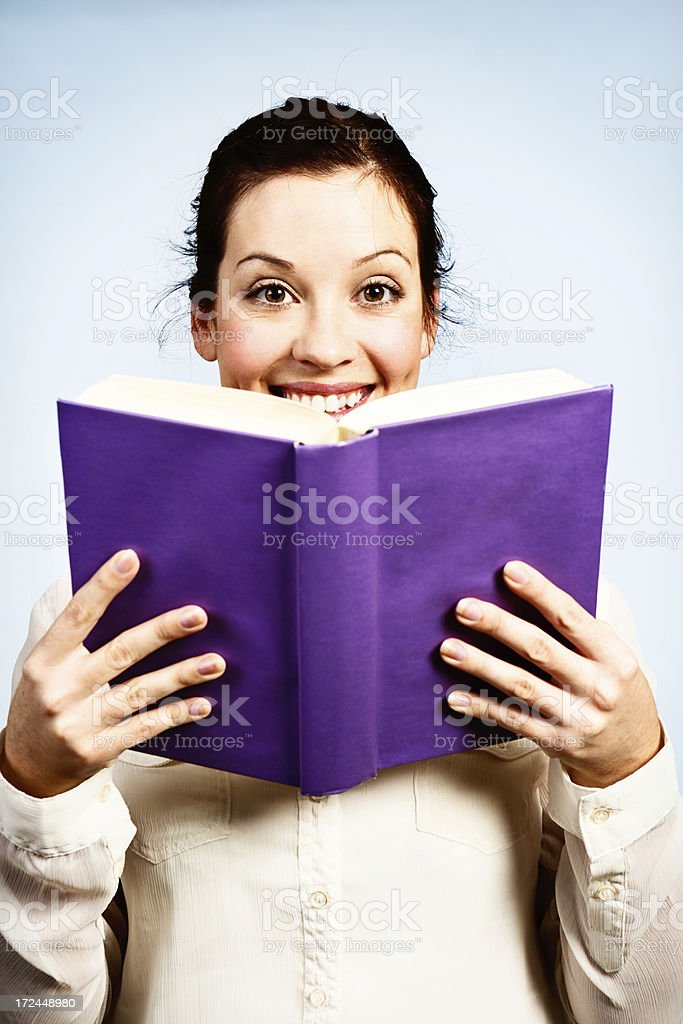 Pretty brunette enjoys reading book with purple cover stock photo