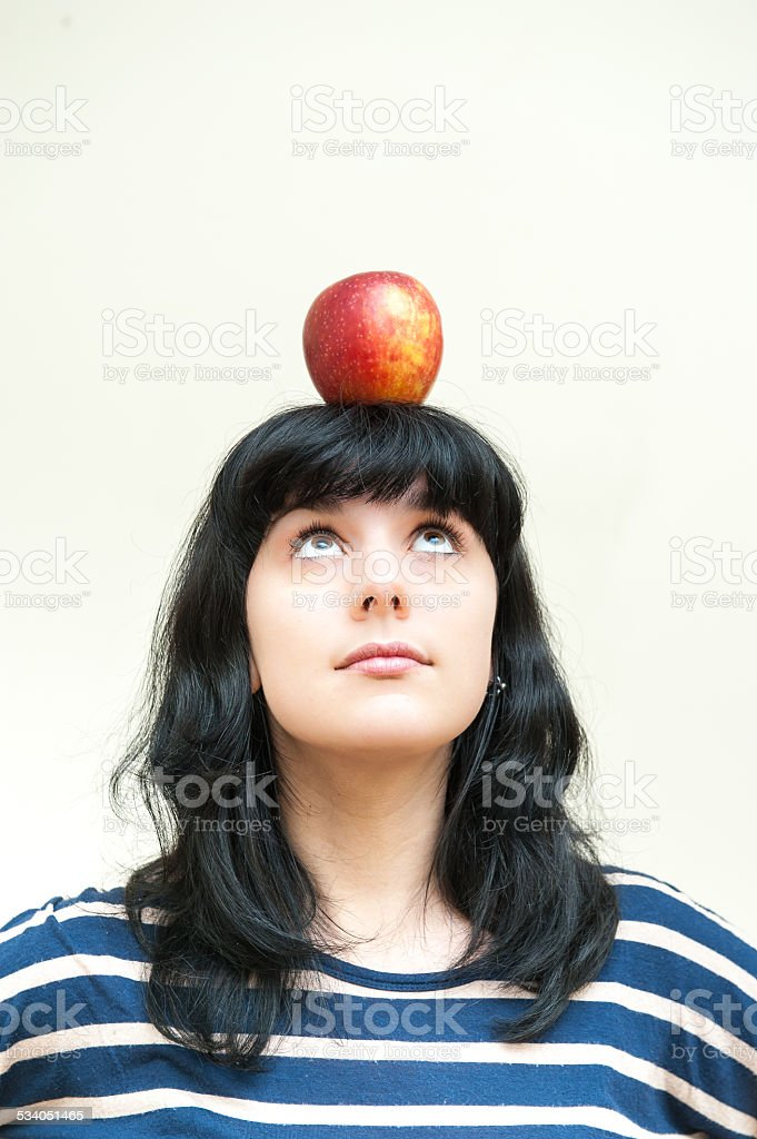 Pretty brunette girl looking red apple on head stock photo