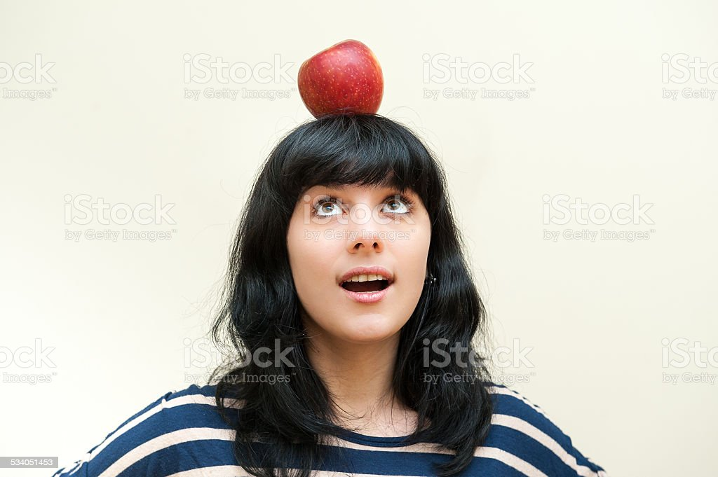 Pretty brunette girl smiling and looking red apple on head stock photo