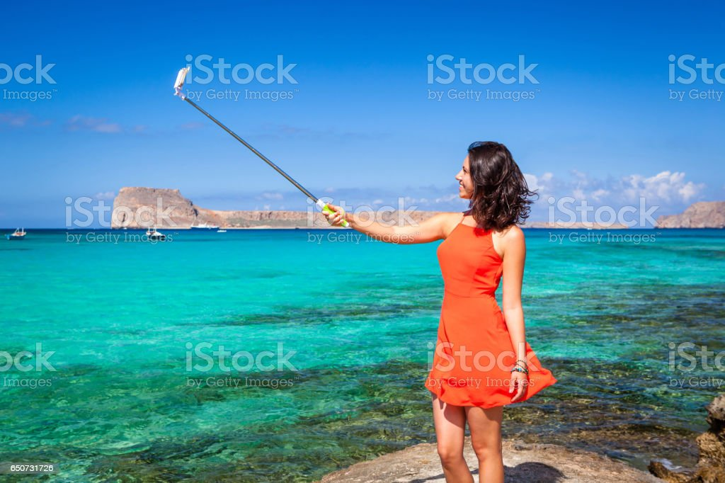 Pretty brunette making selfie with a stick stock photo