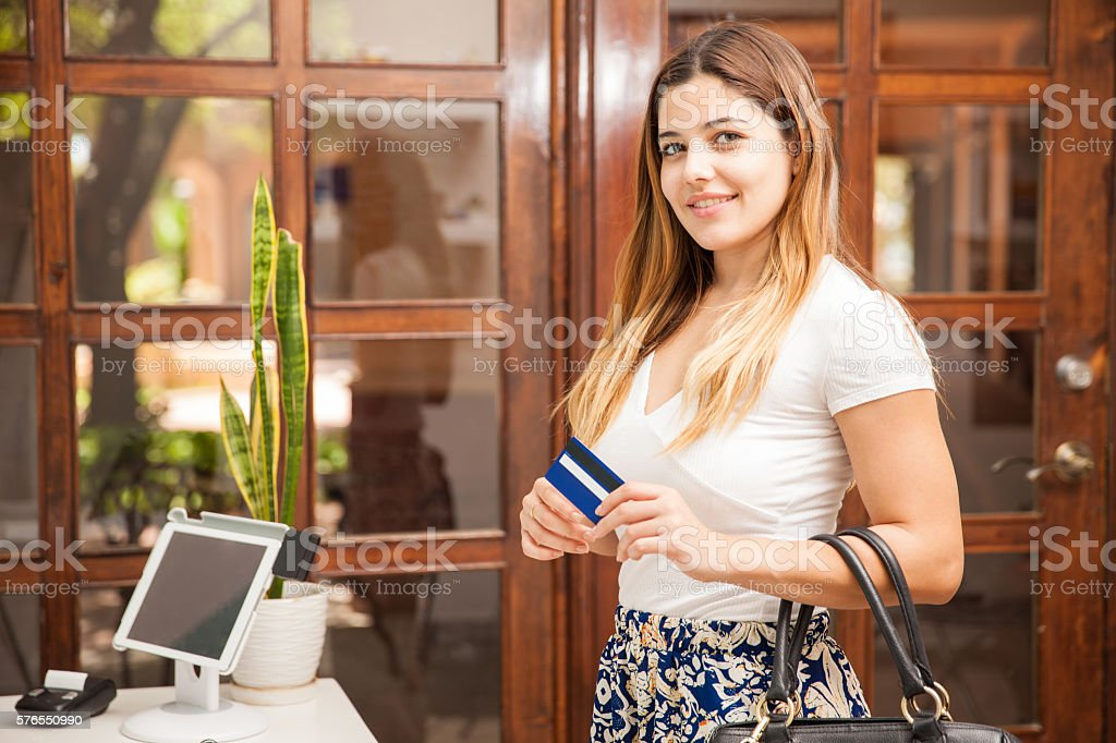Pretty brunette paying with a credit card stock photo
